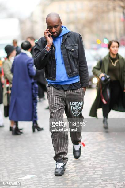 Virgil Abloh wears a blue hoodie sweater, a gray denim jacket, a black t-shirt, gray striped Loewe pants, and black sneakers with white shoe lace,...