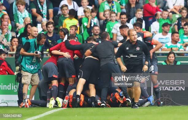 Virgil Misidjan of Nuernberg is mobbed by team mates in celebration as he scores hsi team's first goal during the Bundesliga match between SV Werder...