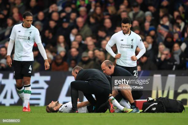 Virgil van Dijk and Alex OxlaideChamberlain look on as Adam Lallana of Liverpool is treated for injury during the Premier League match between...