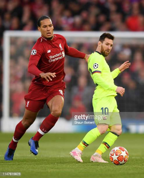 Virgil van Dijk of Liverpool and Lionel Messi of Barcelona watch the ball during the UEFA Champions League Semi Final second leg match between...