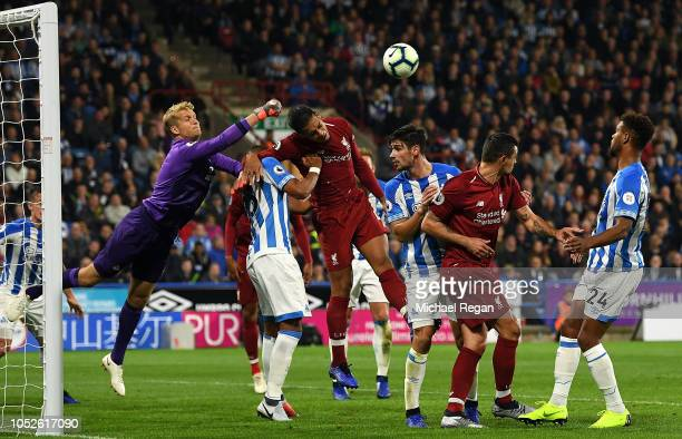 Virgil Van Dijk of Liverpool attempts to win the aerial ball as Jonas Lossl of Huddersfield Town attempts to punch the ball clear during the Premier...