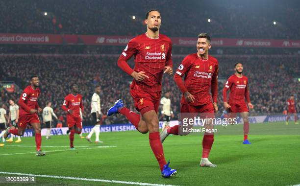 Virgil van Dijk of Liverpool celebrates with Roberto Firmino after scoring his team's first goal during the Premier League match between Liverpool FC...