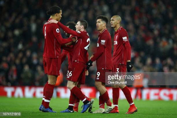 Virgil van Dijk of Liverpool celebrates with team mates Andy Robertson Roberto Firmino and Fabinho following their side's victory the Premier League...