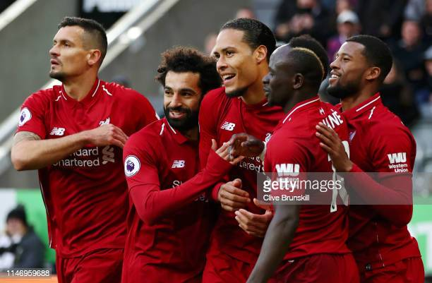 Virgil van Dijk of Liverpool celebrates with teammates after scoring his team's first goal during the Premier League match between Newcastle United...
