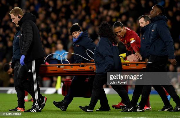 Virgil van Dijk of Liverpool consoles with Gerard Deulofeu of Watford as he is stretchered off with an injury during the Premier League match between...