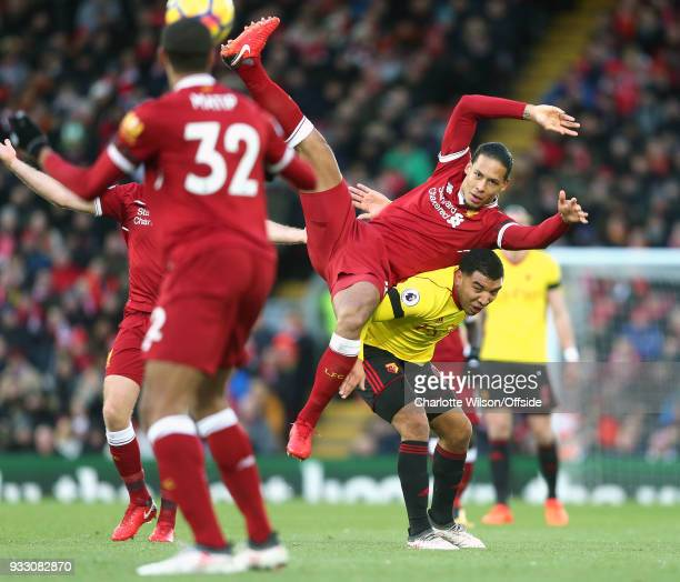 Virgil van Dijk of Liverpool falls across Troy Deeney of Watford as he comes down from a header during the Premier League match between Liverpool and...