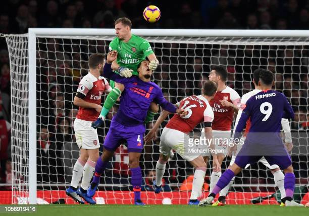 Virgil van Dijk of Liverpool heads the ball and hits the post as he collides with Bernd Leno of Arsenal during the Premier League match between...