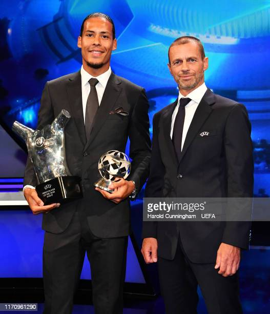 Virgil van Dijk of Liverpool holds his UEFA Champions League Defender of the Season 2018/19 and UEFA Men's Player of the Yeat 2018/19 Awards next to...