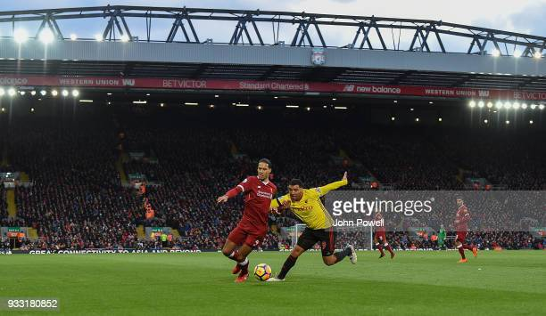 Virgil van Dijk of Liverpool in action with Troy Deeney of Watford during the Premier League match between Liverpool and Watford at Anfield on March...