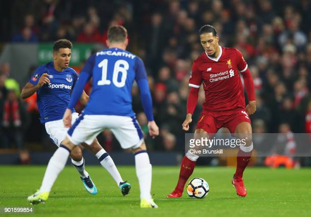 Virgil van Dijk of Liverpool is watched by Dominic CalvertLewin and James McCarthy of Everton during the Emirates FA Cup Third Round match between...