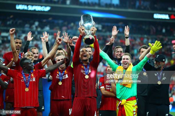 Virgil van Dijk of Liverpool lifts the trophy with his team-mates at the end of the UEFA Super Cup match between Liverpool and Chelsea at Vodafone...