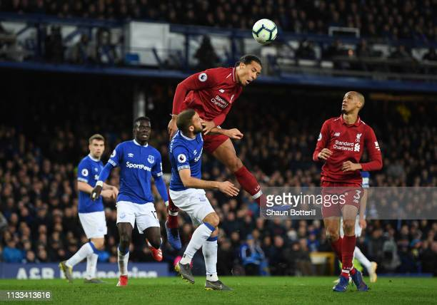 Virgil van Dijk of Liverpool outjumps Cenk Tosun of Everton during the Premier League match between Everton FC and Liverpool FC at Goodison Park on...