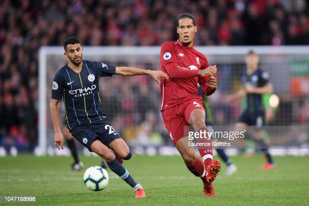 Virgil van Dijk of Liverpool passes the ball under pressure from Riyad Mahrez of Manchester City during the Premier League match between Liverpool FC...