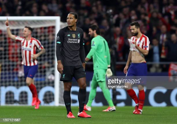 Virgil van Dijk of Liverpool reacts as Saul Niguez of Atletico Madrid celebrates scoring his sides first goal during the UEFA Champions League round...