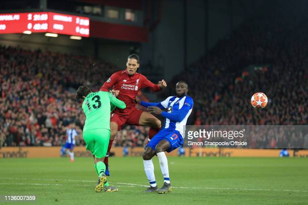 Virgil van Dijk of Liverpool runs into Liverpool goalkeeper Alisson Becker as tha ball bounces away from Moussa Marega of Porto during the UEFA...