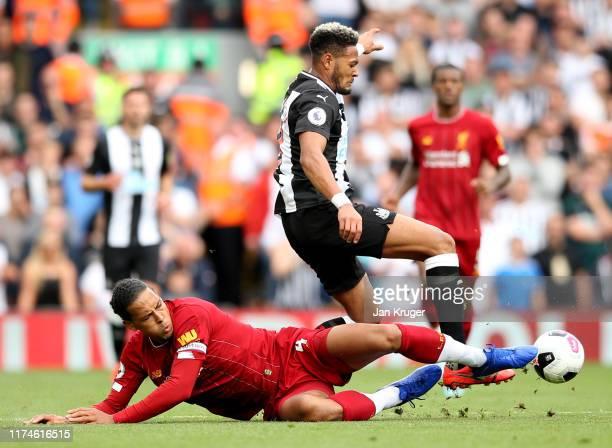 Virgil van Dijk of Liverpool tackles Joelinton of Newcastle United during the Premier League match between Liverpool FC and Newcastle United at...