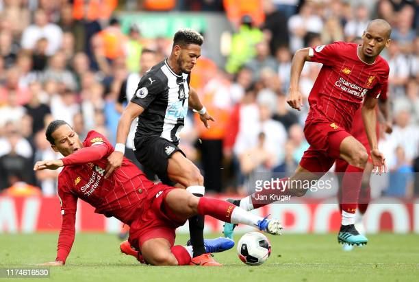 Virgil van Dijk of Liverpool tackles Joelinton of Newcastle United during the Premier League match between Liverpool FC and Newcastle United at...
