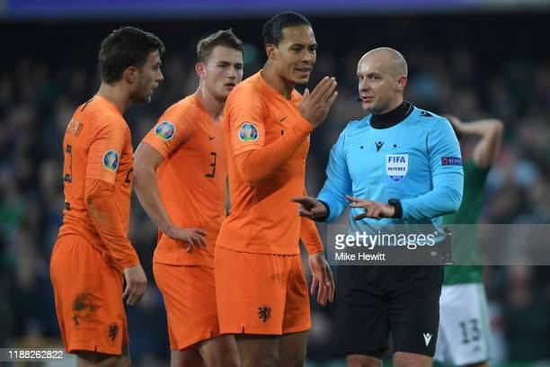 Virgil van Dijk of Netherlands argues with referee Szymon Marciniak of Poland for awarding a penalty to Northern Ireland during the UEFA Euro 2020...