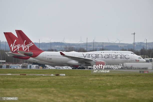 Virgin Atlantic planes sit on the runway at Glasgow Airport on March 21, 2020 in Glasgow, Scotland. Coronavirus has spread to at least 186 countries,...