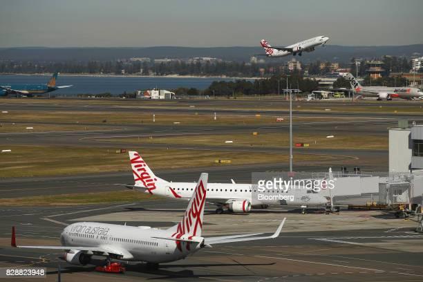 Virgin Australia Holdings Ltd aircraft stand at Sydney Airport in Sydney Australia on Thursday Aug 10 2017 Virgin Australia said underlying...