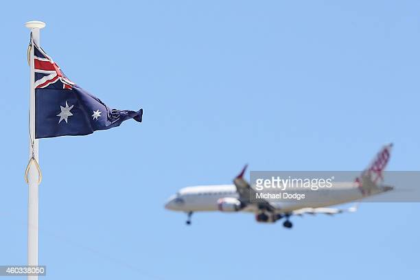 Virgin Australia plane flies behind an Australian Flag during day four of the First Test match between Australia and India at Adelaide Oval on...