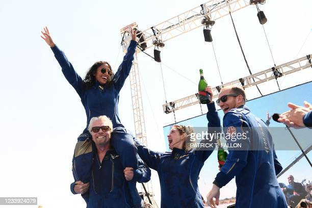 Virgin Galactic founder Sir Richard Branson, with Sirisha Bandla on his shoulders, cheers with crew members after flying into space aboard a Virgin...