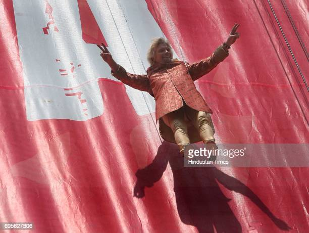 virgin group chairman richard branson dangles on ropes during a launch performence of virgin mobile services in india through tata teleservices at...