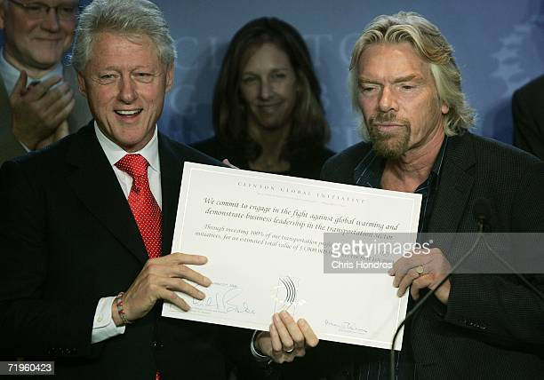 Virgin Group Ltd CEO Sir Richard Branson holds a signed pledge with former US President Bill Clinton at the Clinton Global Initiative annual meeting...