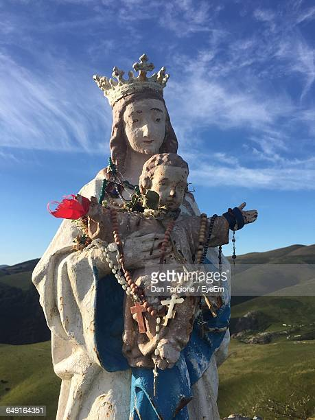 virgin mary and jesus christ statue on field against sky - saint jean pied de port stock photos and pictures
