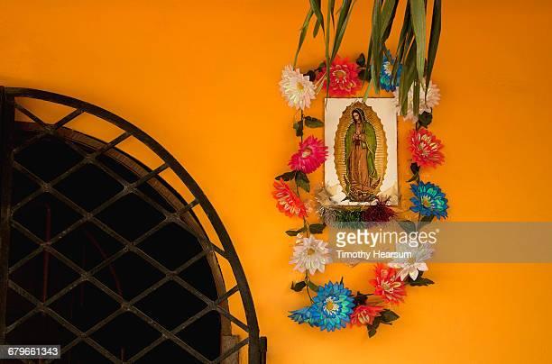 virgin mary plaque with flowers on colorful wall - virgen de guadalupe fotografías e imágenes de stock