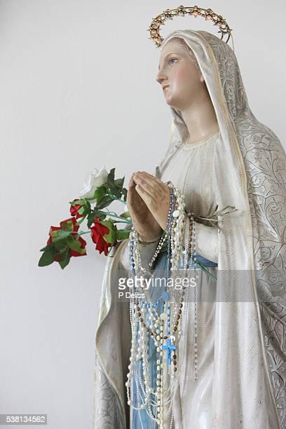 virgin mary sculpture in sacred heart catholic syriac church. mary holding prayers beads. - madonna del rosario foto e immagini stock