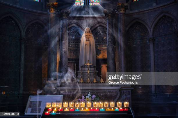 virgin mary statue and candles burning - ardennes department france stock photos and pictures