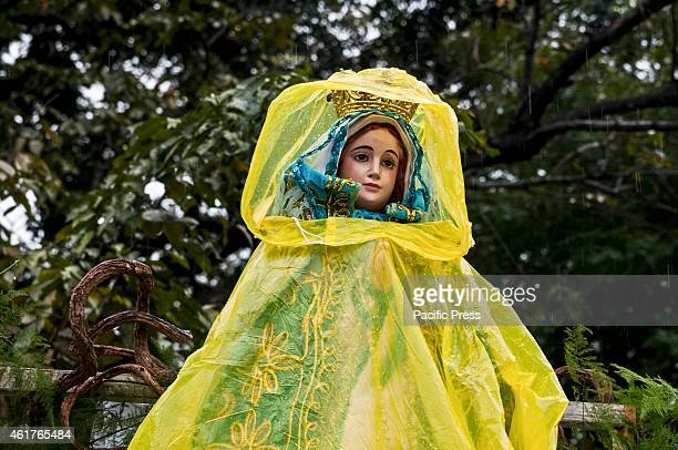 A virgin Mary statue is covered with a yellow raincoat during the rainy final mass of Pope Francis in Quirino grandstand