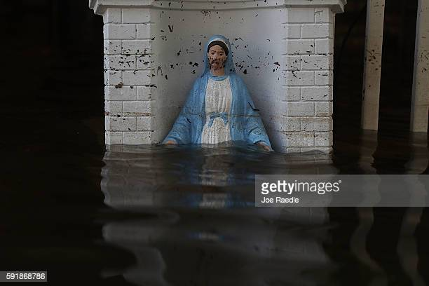 Virgin Mary statue is seen in front of a flooded home on August 18, 2016 in St Amant, Louisiana. Last week Louisiana was overwhelmed with flood water...