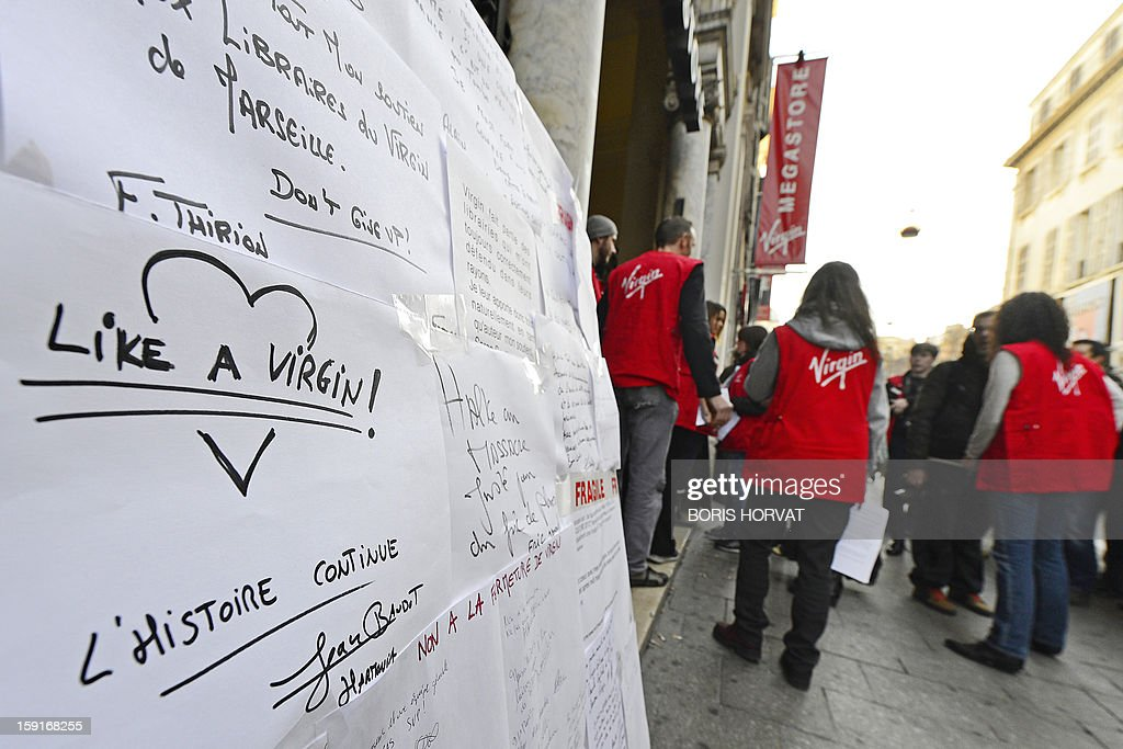 Virgin Megastore employees distribute pamphlets to customers during a demonstration against planned job cuts at the entrance of the store on January 9, 2013 in Marseille, eastern France. Virgin's Megastore music and book unit, which is known in France as a 'culture' retailer, said it will file for insolvency on January 9, 2013. Originally started by Richard Branson, the British billionaire and chairman of the Virgin Group, the Virgin Megastores were bought by the French Lagardere group in 2001.