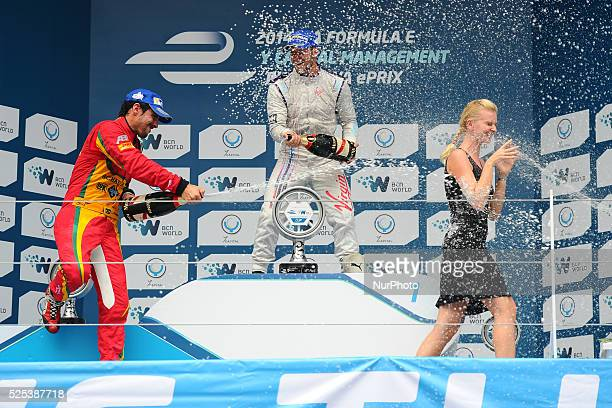 Virgin Racing driver Sam Bird of Great Britain centre celebrates with Audi Sport ABT driver Lucas di Grassi of Brazil left by spraying champagne on...
