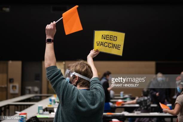 Virgina Mason advanced registered nurse practitioner Erin Forsythe holds up a sign and a flag asking for another patient to dose with the Pfizer...