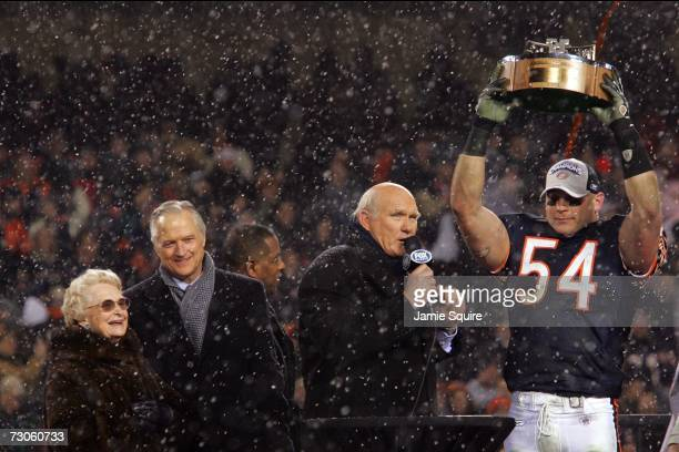 Virginia and Michael McCaskey looks on as Brian Urlacher of the Chicago Bears is interviewed by Terry Bradshaw while holding up the George S Halas...