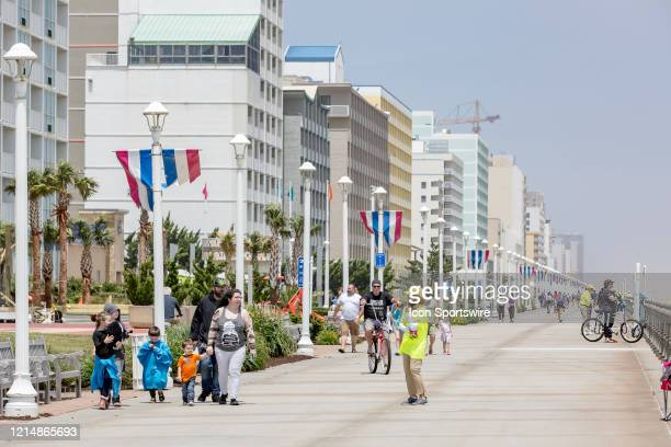 Virginia Beach worker in a yellow shirt and hat greets families along the boardwalk on May 22 in Virginia Beach VA This is the first day of the...