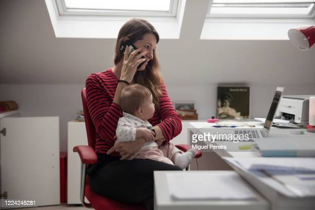 Virginia Bejar, the photographer's partner, strives to work at home while holding her six-month-old daughter Olivia, also the photographer's...
