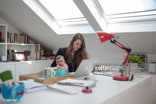 Virginia Béjar holds her 5-month old daughter while working from home during the COVID lockdown on April 14 in Majadahonda, Madrid, Spain. More than...