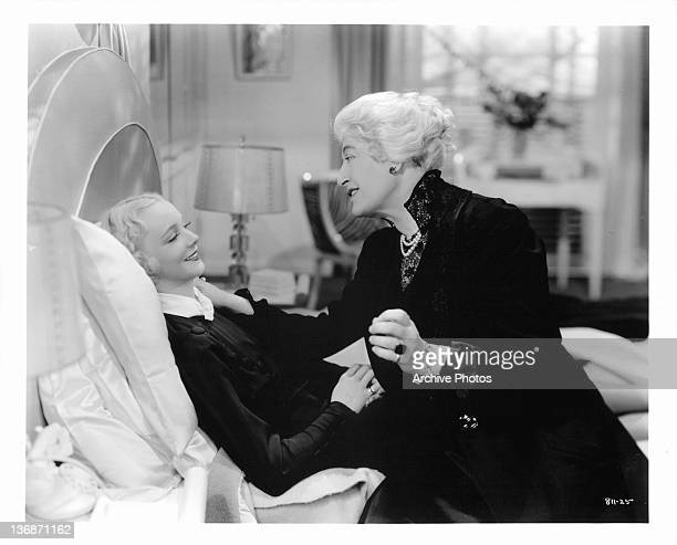 Virginia Bruce laying on a bed as Constance Collier comforts her in a scene from the film 'Shadow Of A Doubt' 1935