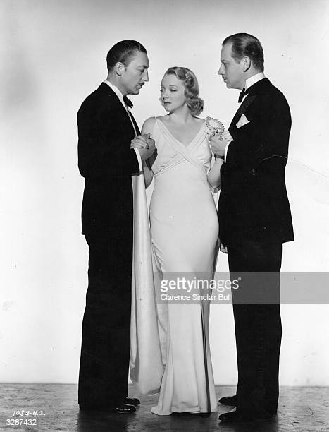 Virginia Bruce the American actress with her two suitors Melvyn Douglas and Warren Williams both American leading men in a still for the MGM film...