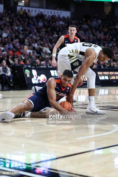 Virginia Cavaliers forward Isaiah Wilkins holds onto the ball despite the attempts by Wake Forest Demon Deacons forward Terrence Thompson to hold it...