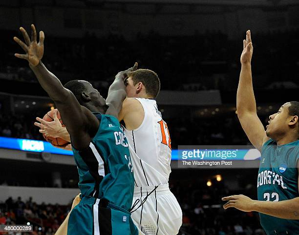 Virginia Cavaliers guard Joe Harris takes a hand to the face from Coastal Carolina Chanticleers center El Hadji Ndieguene as he drives to the basket...