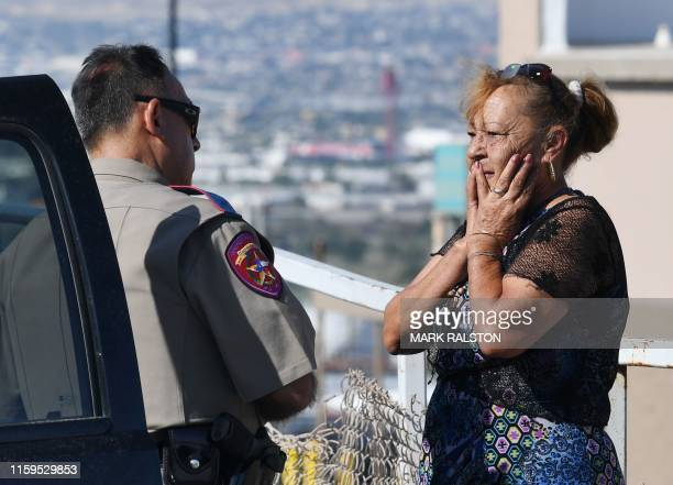 Virginia Chacon reacts as she tells her survival story to a police officer outside the Cielo Vista Mall Wal-Mart where a shooting left 20 people dead...
