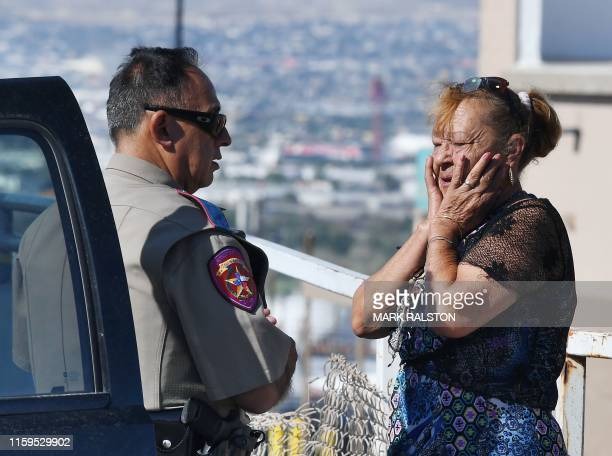 Virginia Chacon reacts as she tells her survival story to a police officer outside the Cielo Vista Mall WalMart where a shooting left 20 people dead...