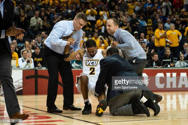Virginia Commonwealth University Rams Guard Marcus Evans injures his left knee and is helped off the court during the first half of the game between...
