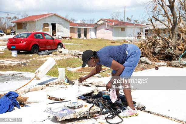 Virginia Cooper picks through a pile of her belongings on the foundation that is all that is left of her home after Hurricane Dorian swept it away in...