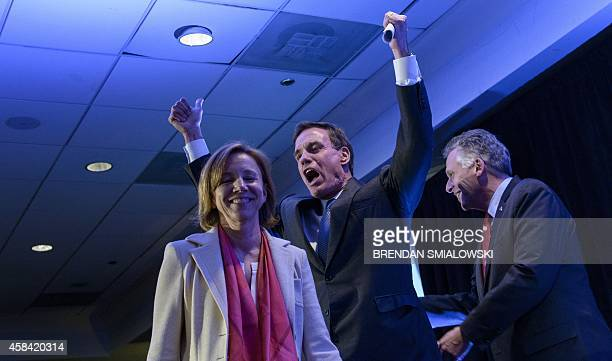 Virginia Democratic Senator Mark Warner cheers as he walks to the stage with his wife Lisa Collis and Virginia Governor Terry McAuliffe during an...